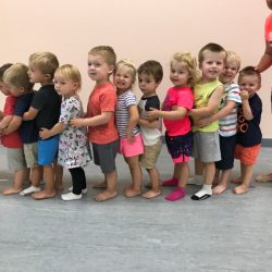 A picture of a group of toddlers standing in a line - Leaps and Bounds
