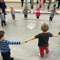A picture of group of toddlers holding hands in a circle - Leaps and Bounds