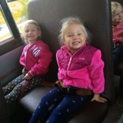A picture of two preschoolers sitting in a bus - Leaps and Bounds