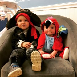 A picture of two infants sitting in costume - Leaps and Bounds