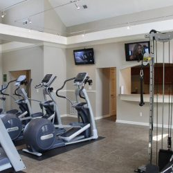 Our gym with treadmills, weight machines, and TV - The Legends Apartments