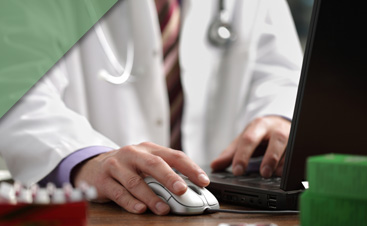 An image of a doctor operating a computer.