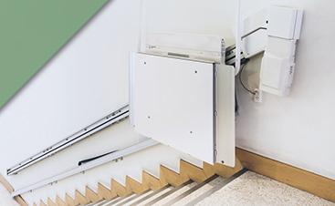 A white stair lift chair against a white wall.