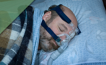 An image of a man in a plaid robe sleeping with a sleep apnea mask on.
