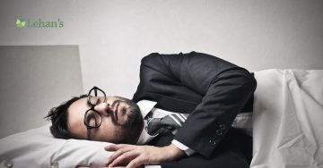 A business man sleeping in his full suit under the covers.
