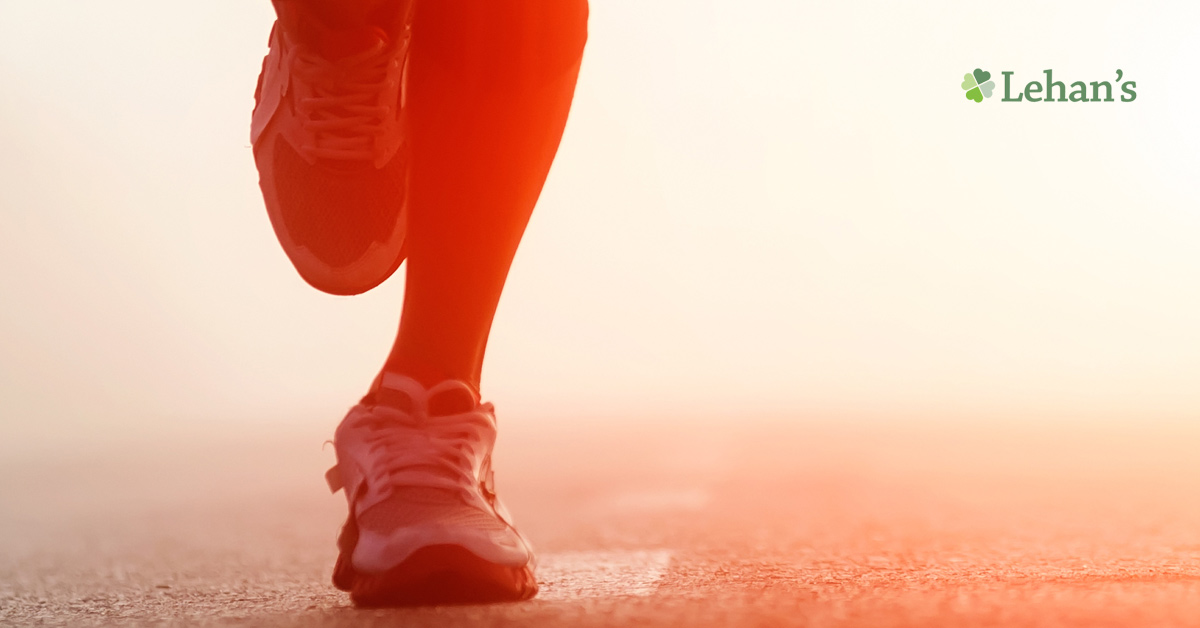 A close up of a person running across asphalt.