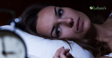 An image of a woman in bed staring at the clock.