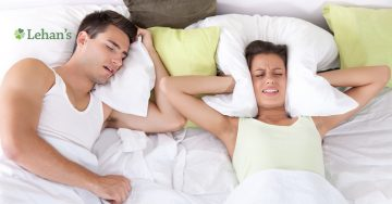 A woman lays next to a sleeping man holding a pillow around her ears.