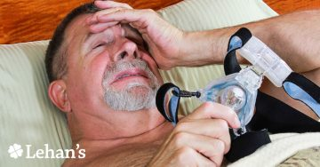 A man in distress holding a CPAP mask.