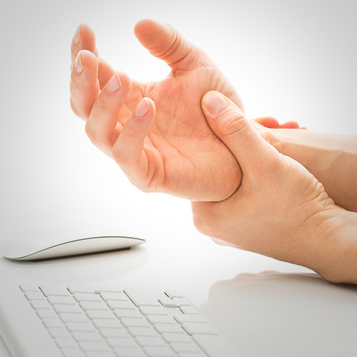 An image of a person gripping their hand in front of a keyboard.