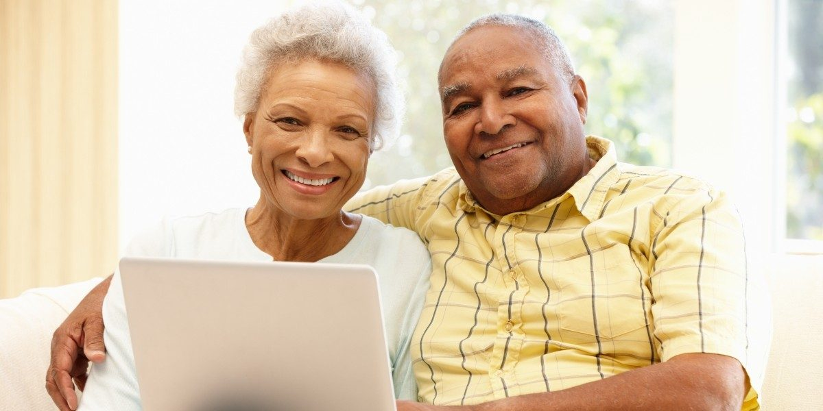A older black couple smile at the camera.