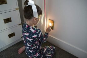 Picture of little girl using the built in night light. You push the on the light and a portable flash light pops out.