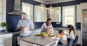 Image of a mom helping her two young children with homework at the kitchen island with beautiful pendant lights hanging down
