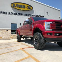 lifted red truck at LINE-X of Austin