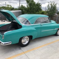 open trunk on classic teal car at LINE-X of Austin