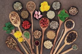 Spices and Health Foods in Bowls and Wooden Spoons