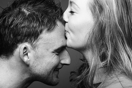 woman kissing man on forehead
