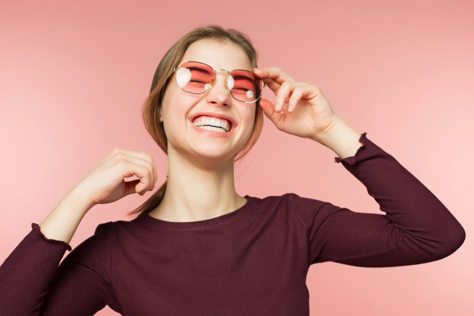 Woman Smiling With Rose Colored Glasses