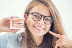 Young Girl Holding Braces Model