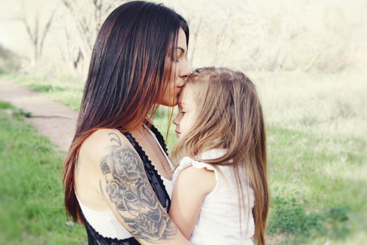 Mother kissing daughter on the head photograph