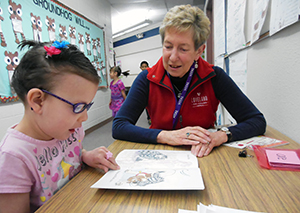 Seven-year-old Amelia North, left, reads out loud with the help of Fran Bostwick Tuesday, Feb. 11, at B.F. Kitchen Elementary School. Bostwick, a member of the Loveland Rotary Club, is tutoring the second-grader as part of the service's club's pilot literacy program at the school and at B.F. Kitchen Elementary School. (Photo by Shelley Widhalm/Loveland Reporter-Herald)