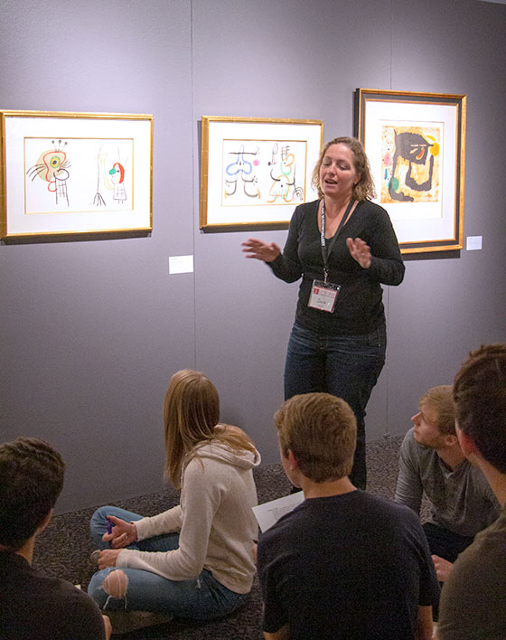 Museum volunteer giving a lecture on the art on display to high school students