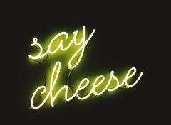 "A neon yellow sign that says ""say cheese"""