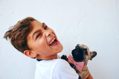 An image of a young child smiling and holding a puppy.