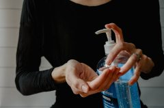 An image of a person holding a bottle of hand sanitizer.