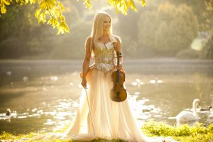 Celtic fiddler Mairead Nesbitt poses with her violin in front of a pond.
