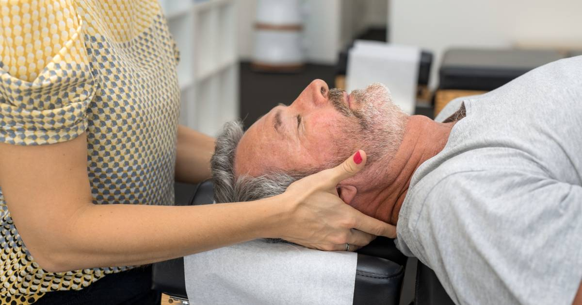 Man getting adjusted by female chiropractor