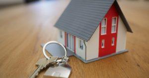 Small house model next to house keys.