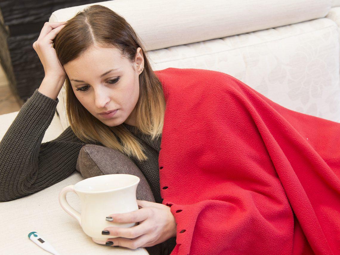 Woman on the sofa feeling ill.