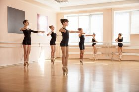 Image of several ballet dancers balancing on their toes