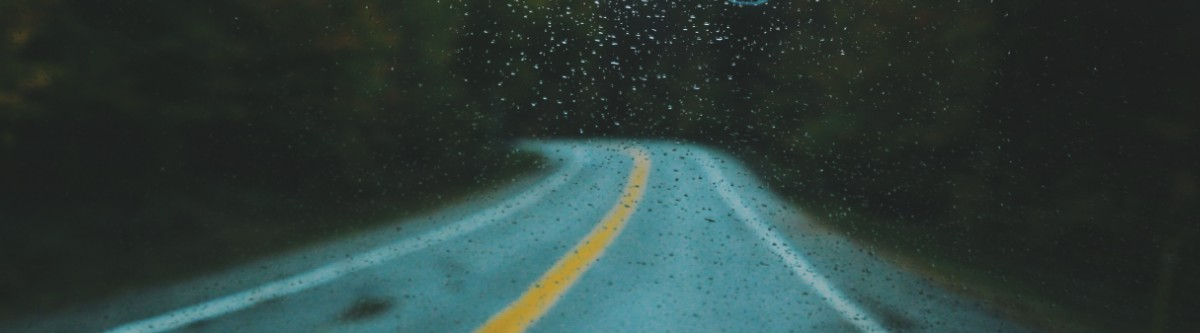 image of road on rainy day through a windshield