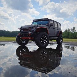Jeep Rubicon parked over water with it's reflection.