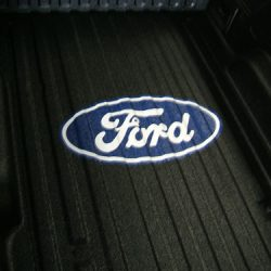Zoomed shot of Ford symbol installed in truck bed by LINE-X of Indianapolis