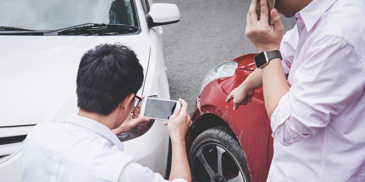 men taking photo and talking after car accident