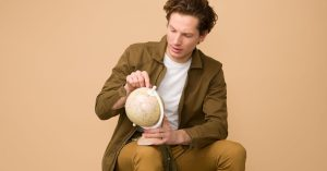 A man sits, holding and looking at a small globe of the world.Photo by Icons8 Team on Unsplash.