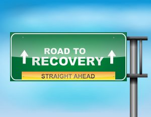 "Highway sign with ""Road to recovery "" text"