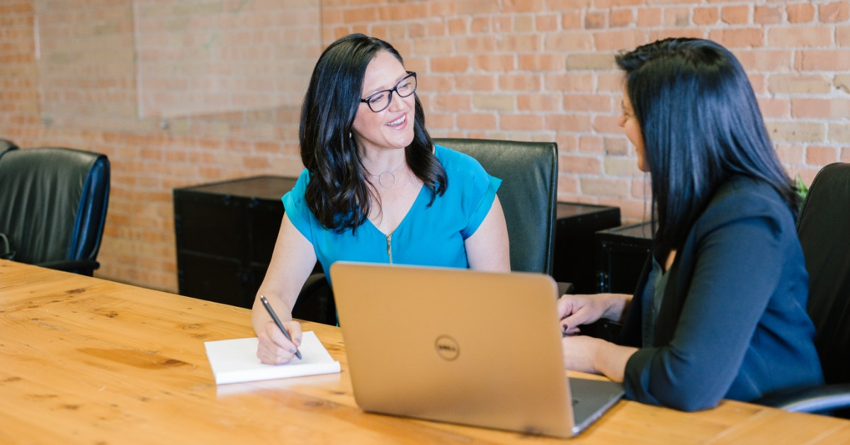 Two businesswomen consulting with each other in front of a computer.