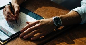 Hands of business person wearing watch and writing in a notepad.