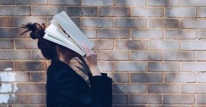 Woman in blue covering her face with a book.