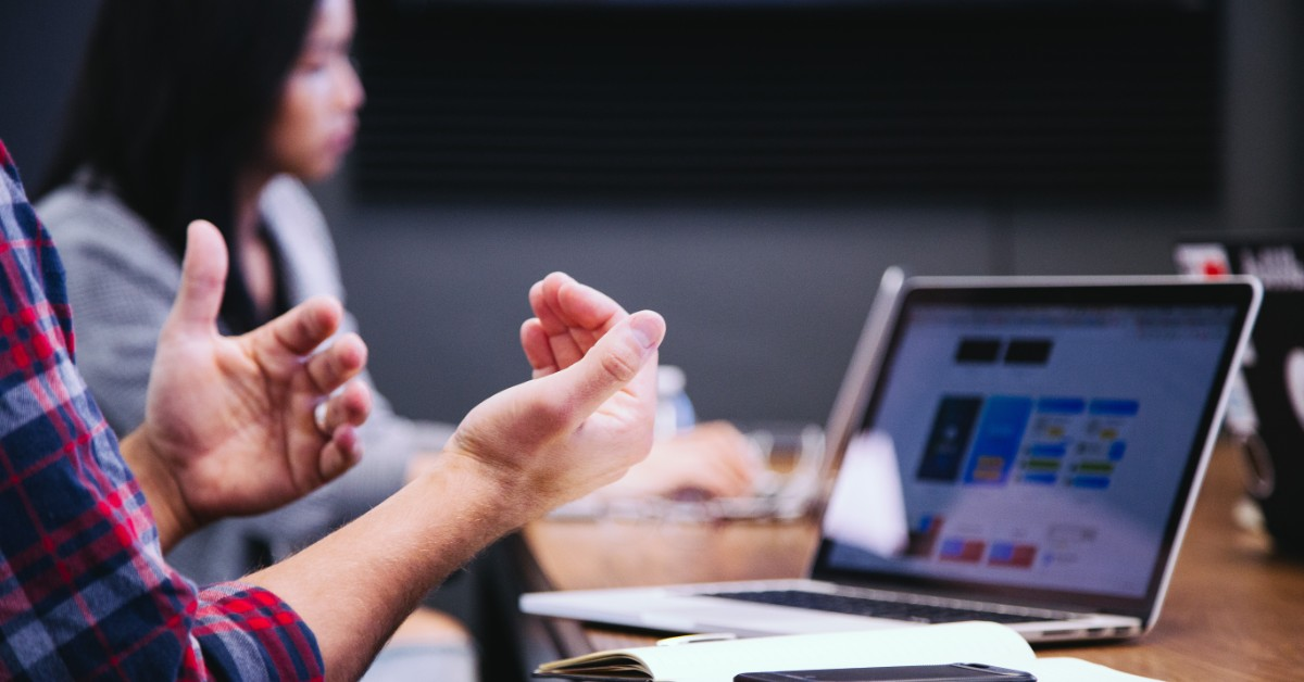 Close up of hands used to explain something on a computer screen, with another person in the background.