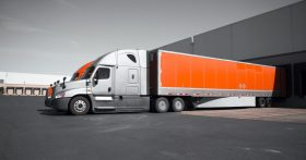 An image of a pair of large orange and silver semi trucks