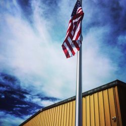 An American flag installed in front of a commercial building - ND Flag Pole Guy