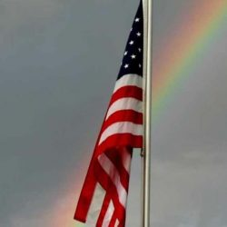 American flag hanging with a rainbow in the background - ND Flag Pole Guy
