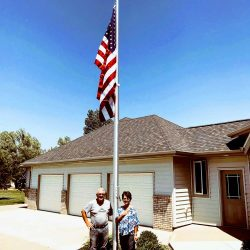 Couple standing by their flag pole installed in front yard - ND Flag Pole Guy