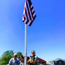 Couple with dog standing next to their flag pole - ND Flag Pole Guy