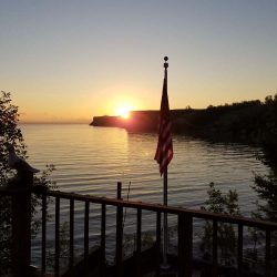 Sunset over a lake with silhouette of a flag pole - ND Flag Pole Guy